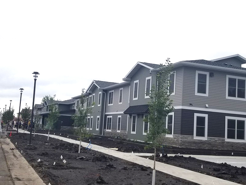 a gray apartment building with newly planted trees